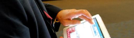 Bild zeigt Tablet in der Hand von einem Mann